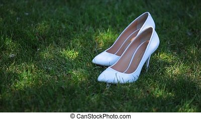 bride's white wedding shoes in the grass.