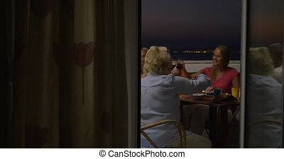 People dining and drinking wine on balcony - Friends or...