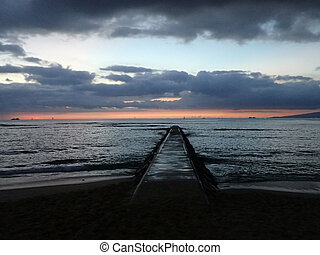 Empty Pier Path on beach at dusk in Waikiki with boats on...