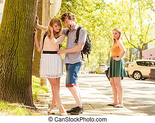 Jealous girl looking at flirting couple outdoor Happy young...