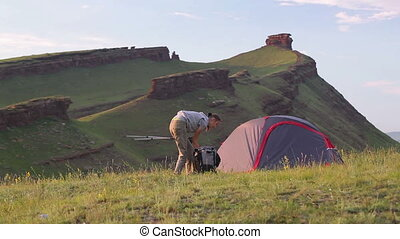 Young woman prepares backpack and walks away from camp -...
