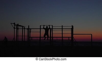 athlete pulls on the bar at sunset on the sea. silhouette