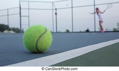 Yellow tennis ball and net on a green court. Slow motion -...