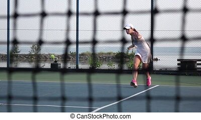 On the tennis court - personal trainer training a tennis...