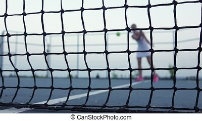 Tennis ball. Tennis net. Slow motion - Girl tennis player...