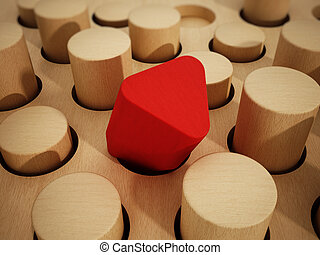 Red prism wooden block standing out among wooden cylinders....