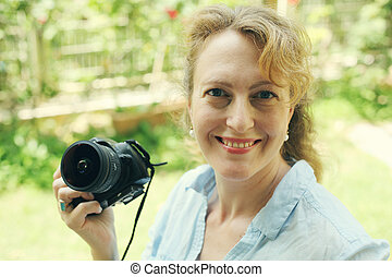 Portrait of beautiful real 40 years old woman holding photo...