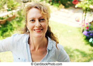 Portrait of beautiful real 40 years old woman in the park