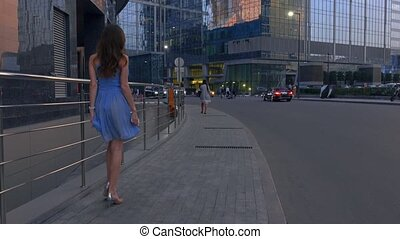 Slim brunette girl in blue dress walking on the street...