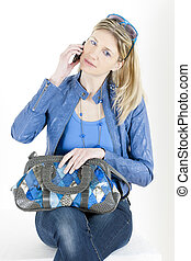 portrait of sitting woman with mobile phone and handbag