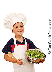 Happy kid with chef hat and a bowl of green peas