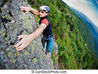 Young white man climbing a steep wall in mountain,...