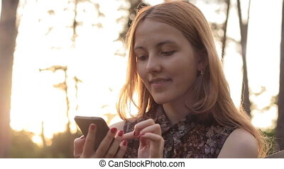 Girl laughing while using mobile phone in countryside -...