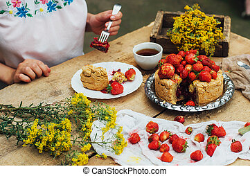 Woman eating a delicious home-made cake with aisheny and stuffed strawberries for dessert. Summer Styled dinner table. Coffee to the cake. sitting at the rustic dining table