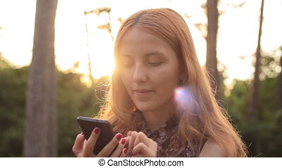 Portrait of smiling happy girl using phone and looking at...