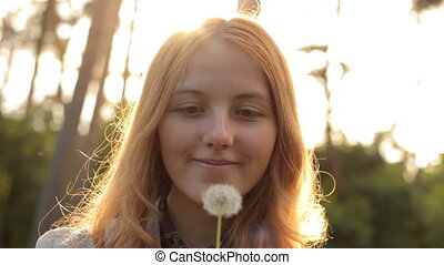 beautiful smiling girl blowing on dandelion and looking at camera