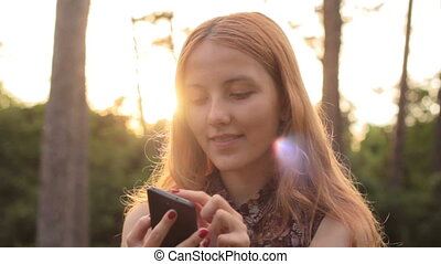 Smiling red-haired girl using smartphone - Portrait of...