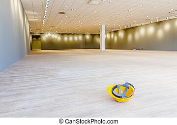 Yellow plastic safety helmet on the floor made of laminate in empty finished modern large showroom
