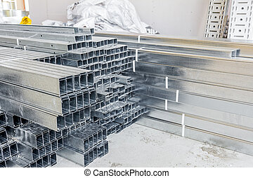 Thin square metal profiles for dry wall stacked on ground -...