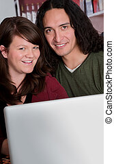 Interracial couple with copy space in front of laptop