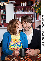 Happy couple - Love and kisses with coffee at a cafe
