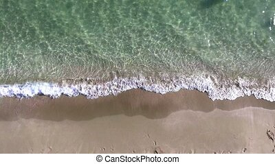Aerial view footage of sea waves reaching shore. Top view on the beautiful sandy beach from copter.