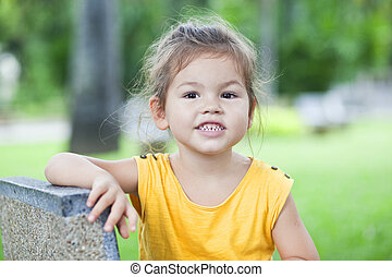 beautiful little girl waves her hand on a background of...