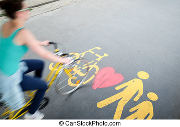 Woman in bike passing by the pedestrian/bicylce sign with heart graffiti on the sidewalk in Budapest
