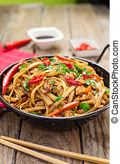 Chinese food on wok - Chicken chow mein a popular oriental...