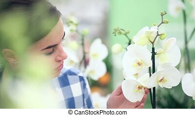 smiling woman in garden of flowers, touches and smells an...