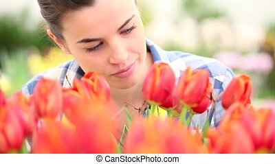 springtime, smiling woman in garden with tulips