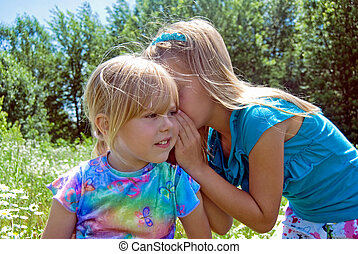 Whispering Secrets - Little girl whispering a secret.