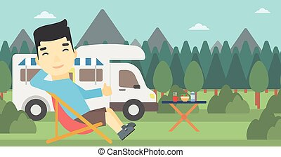 Man sitting in chair in front of camper van. - An asian man...