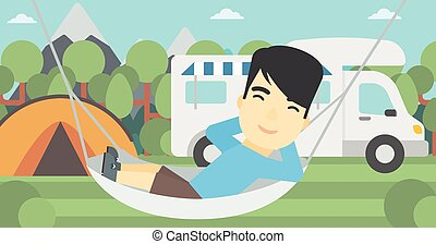 Man lying in hammock in front of motor home - An asian man...