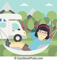 Woman lying in hammock in front of motor home - An asian...