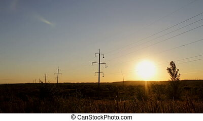 Timelapse high voltage electricity power lines at sunset above the beautiful