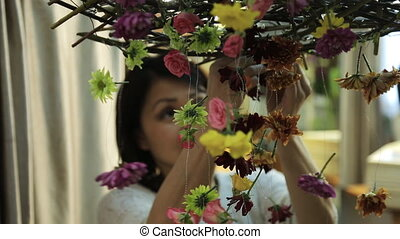 Chinese woman decorates interior of room with floral...