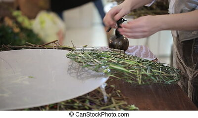 Woman decorates wreath, made from grass, with glass flasks.