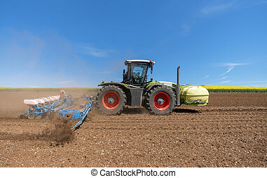Tractor with sowing machine on a field at work
