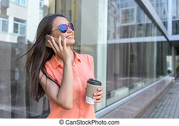Cheerful young woman calling by phone - Carefree girl is...