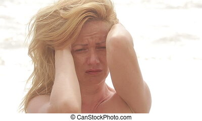 Sad woman crying during storm on the beach. hair fluttering...