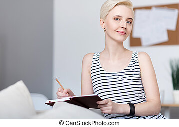 Woman sitting and holding notebook - Calm time. Thoughtful...