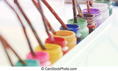 Jars of colorful paint with brushes made out of real...