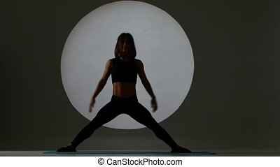 Athlete sits on side splits. Back light. Silhouette - Young...