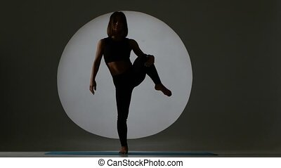 Athlete doing vertical stretching. Back light. Silhouette -...