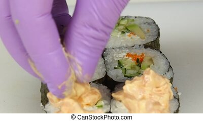 Cook gets sauce on sushi and finalizing Close up - Sushi...