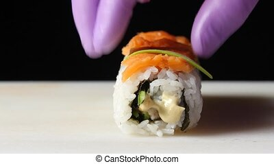 Chef decorates the roll with pieces of avocado Close up -...