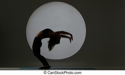 Girl doing bridge on the floor. Back light. Silhouette -...