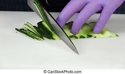 Chef cuts the cucumber. Close up. Slow motion