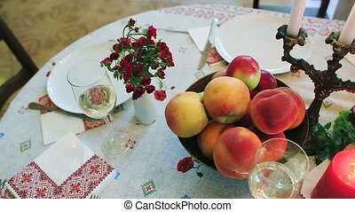 Tableware. On the festive table fruit, red fish, a glass of...